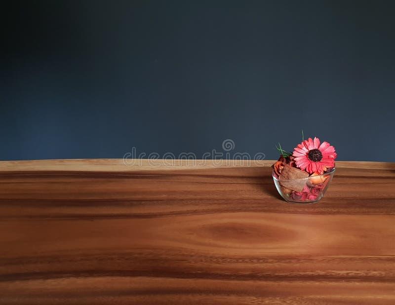 Vetro dei fiori rossi dei potpourri sulla tavola immagine stock libera da diritti