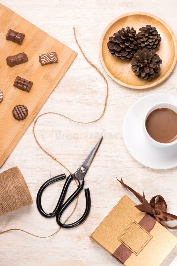 Vetro del cioccolato del latte al cioccolato e di varietà sulla tavola con il contenitore ed il computer portatile di regalo fotografia stock libera da diritti