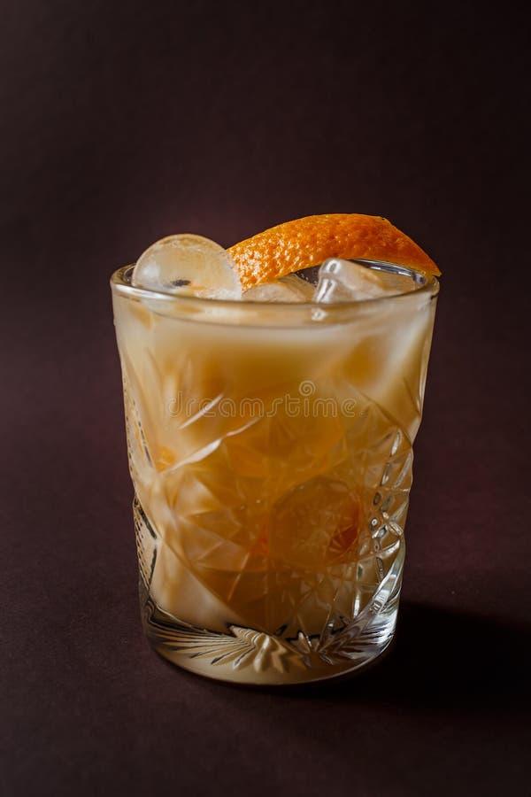 Vetro del cocktail arancio dell'alcool con ghiaccio e fetta di arancia sopra fotografie stock libere da diritti