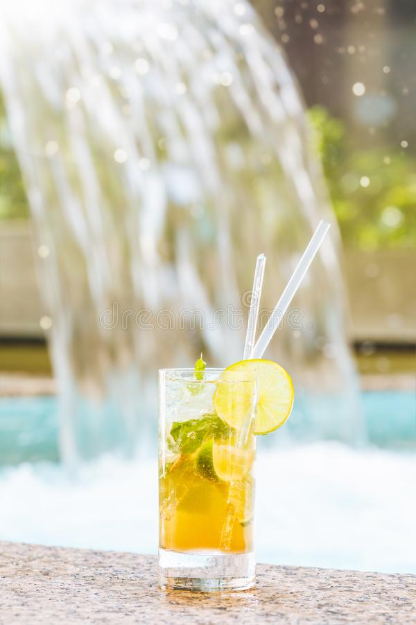 Vetro del cocktail classico di mojito con il caipirinha sul bordo di pietra della piscina immagini stock