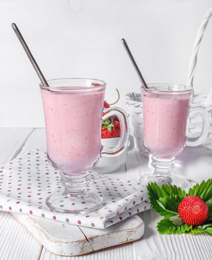 Vetro del frullato fresco del yogurt e della fragola sulla tavola di legno bianca fotografia stock