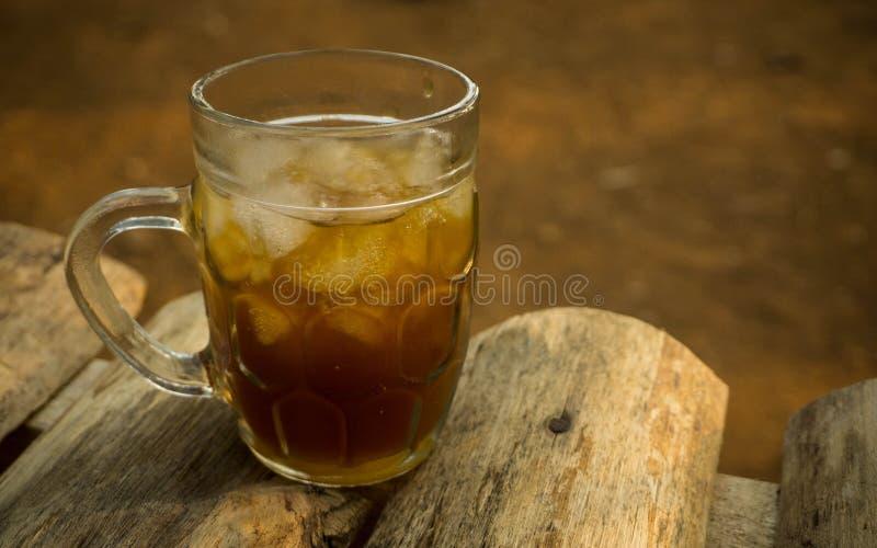 Vetro del liquido di jawa del asem del tè del tamarindo del ghiaccio sulla tavola di legno fotografia stock