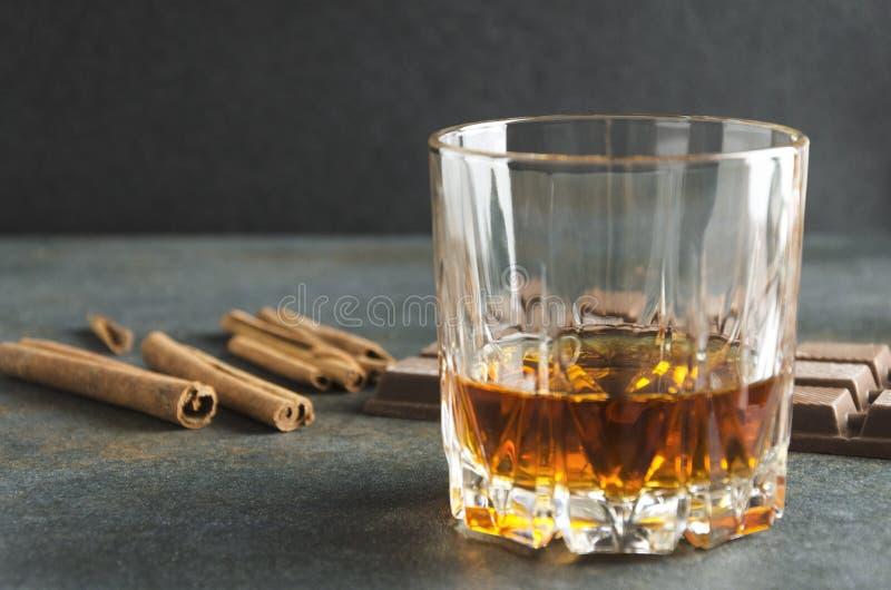 Vetro del reggiseno del brandy, della cannella e del cioccolato sulla tavola grigia Colpo del primo piano immagini stock libere da diritti
