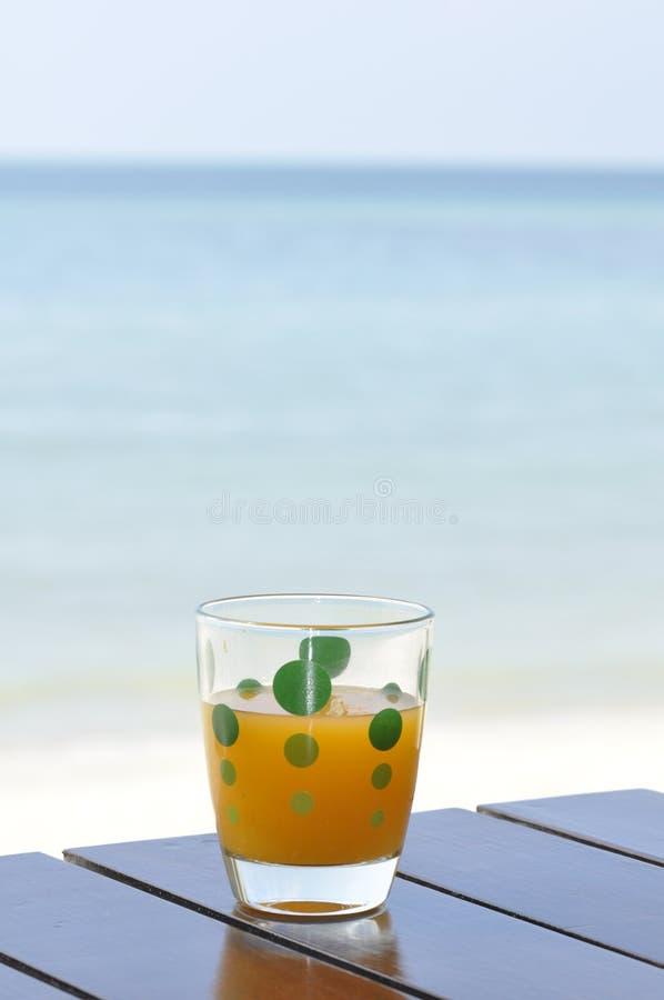 Vetro del succo di arancia alla spiaggia fotografia stock libera da diritti