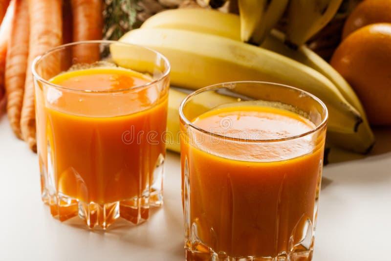 Vetro del succo di frutta con l'arancia, le carote e la banana fotografie stock libere da diritti