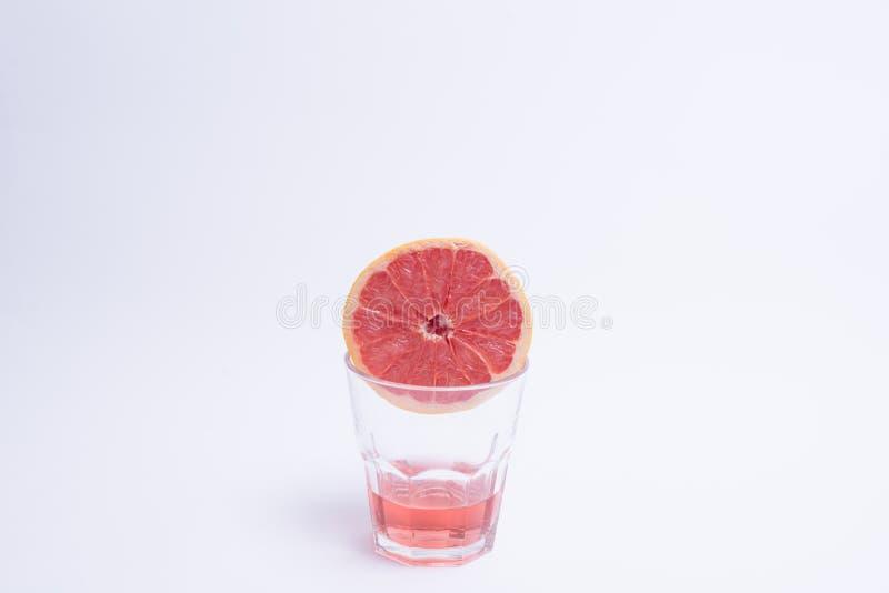 Vetro del succo di pompelmo rosa sopra fondo bianco fotografia stock
