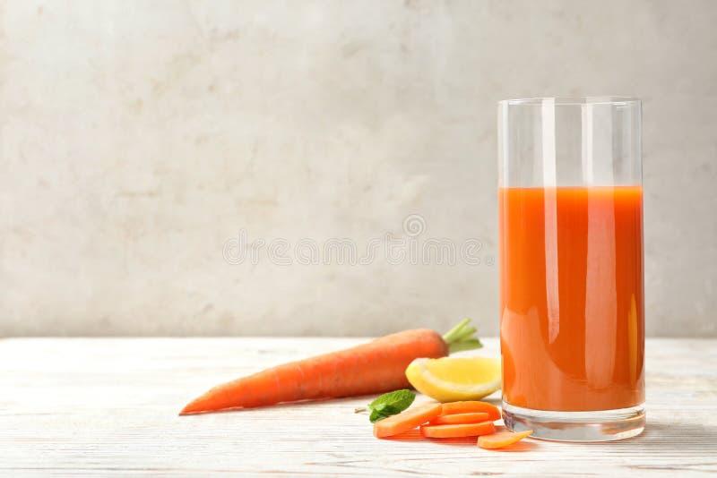 Vetro del succo e degli ingredienti di carota freschi sulla tavola di legno bianca contro fondo leggero fotografia stock