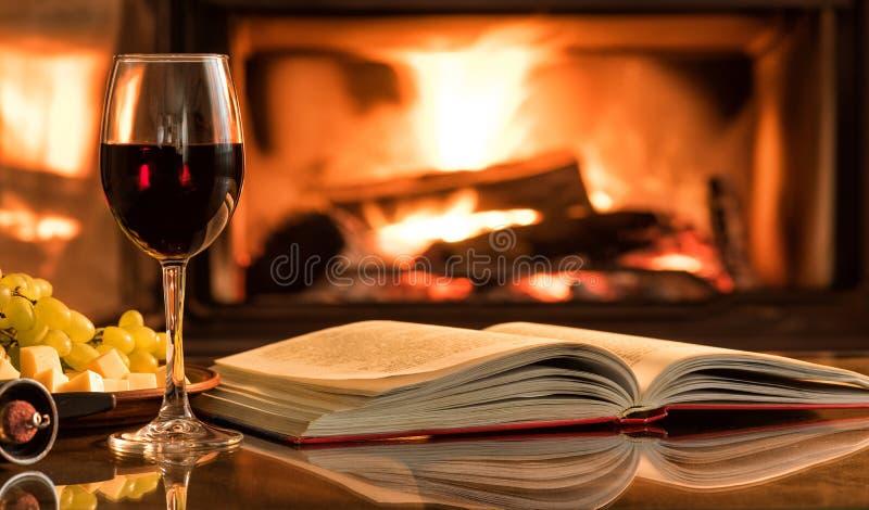 Vetro del vino rosso con un libro aperto sulla tavola immagini stock