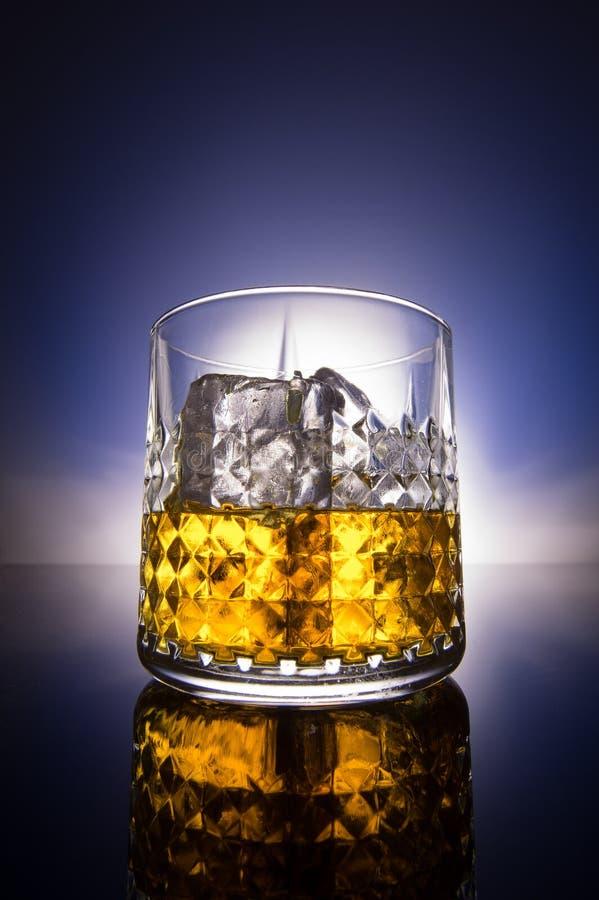 Vetro del whiskey con il fondo di pendenza immagine stock libera da diritti