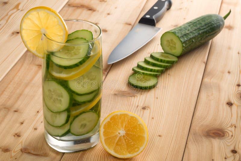 Vetro dell'acqua della disintossicazione con il limone ed il cetriolo su fondo di legno illuminato da contro luce Fuoco molle fotografie stock