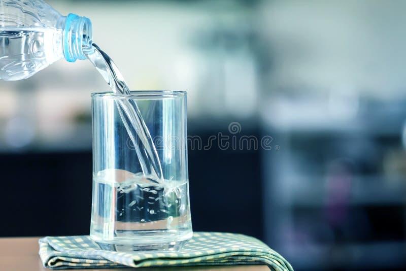Vetro dell'acqua purificata sulla barra della tavola nel kitchenroom fotografie stock