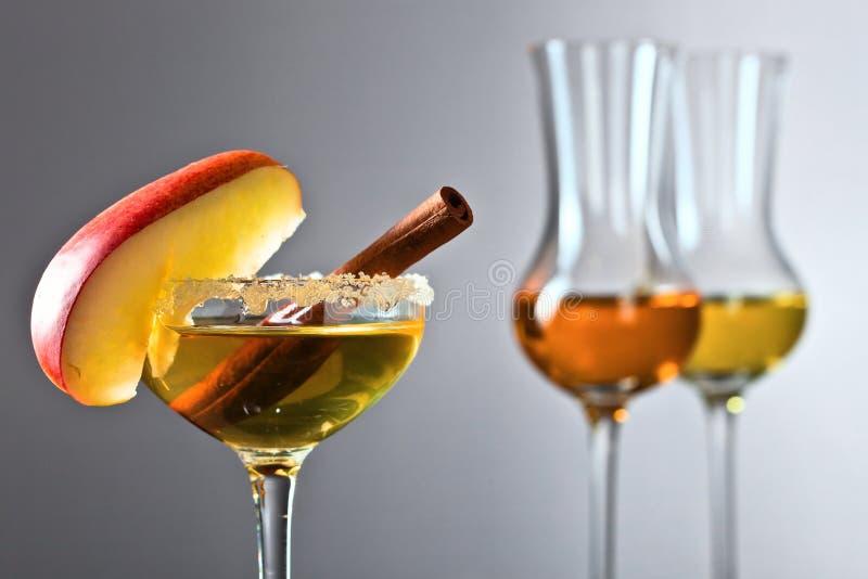 Vetro della bevanda alcolica dolce con la mela e la cannella immagini stock libere da diritti