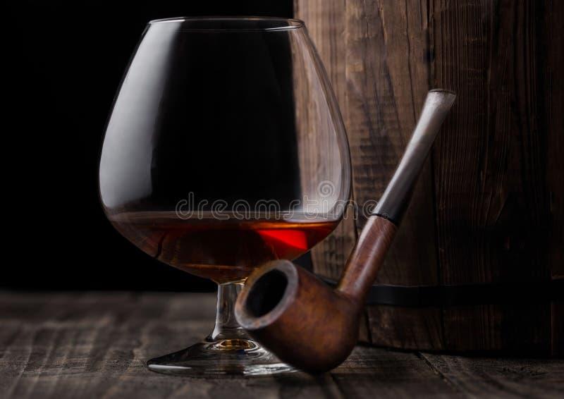 Vetro della bevanda del brandy del cognac e tubo di fumo d'annata accanto al wo immagine stock