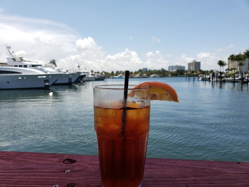 Vetro della bevanda del tè ghiacciato vicino al porticciolo con le barche immagini stock