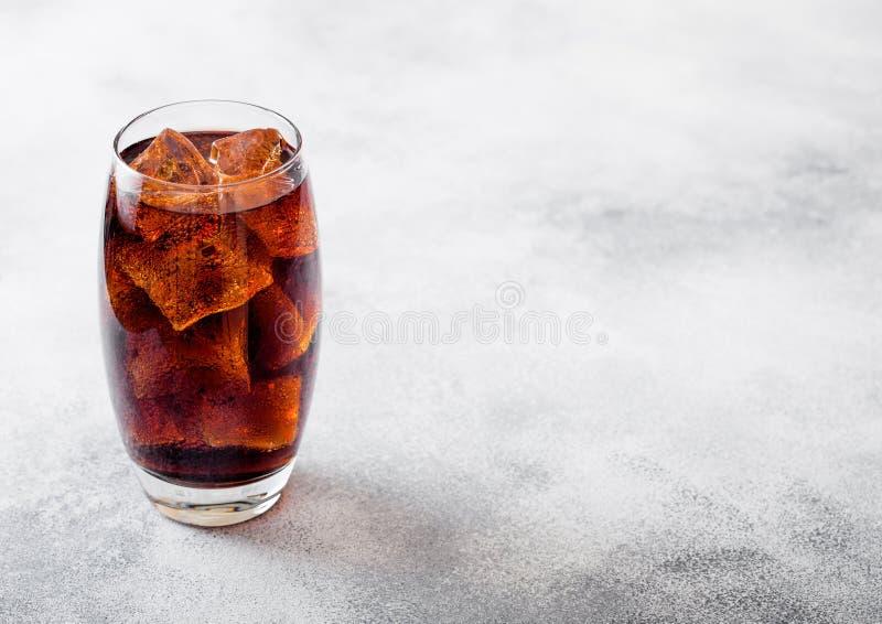 Vetro della bevanda della soda della cola con i cubetti di ghiaccio e le bolle sul fondo di pietra del tavolo da cucina fotografia stock