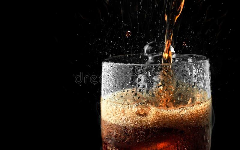 Vetro della bibita con la spruzzata del ghiaccio su fondo scuro Vetro della cola nel concetto del partito di celebrazione fotografia stock libera da diritti