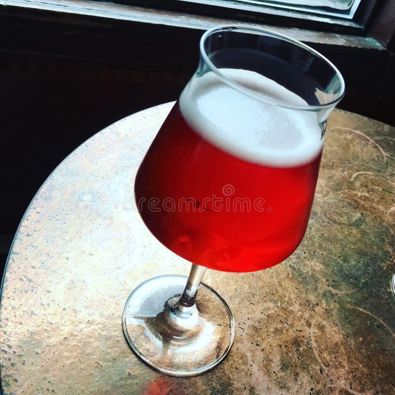 Vetro della birra stagionale della ciliegia su una tavola della barra immagini stock