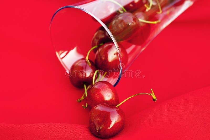 Vetro della ciliegia su una priorità bassa rossa fotografie stock libere da diritti