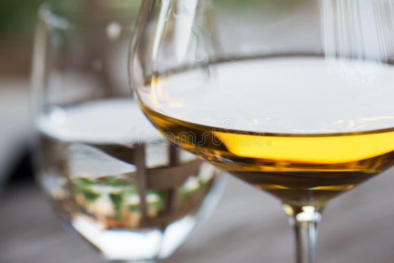 Vetro della fine del vino bianco di Chardonnay su immagine stock libera da diritti