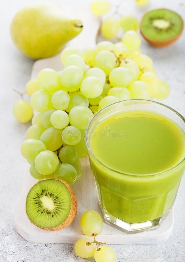 Vetro della frutta tonificata verde organica del frullato fresco su chopp bianco immagine stock libera da diritti