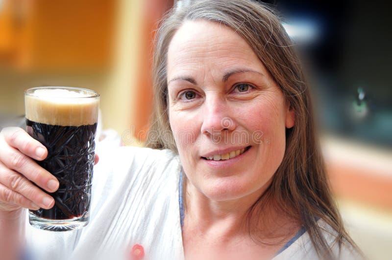 Vetro della holding della donna di birra immagine stock