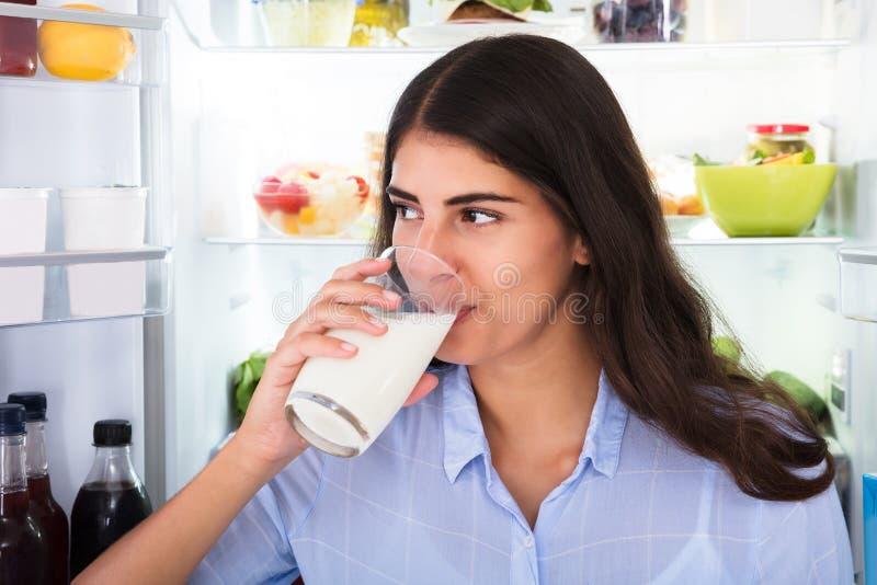 Vetro della holding della giovane donna di latte fotografia stock libera da diritti