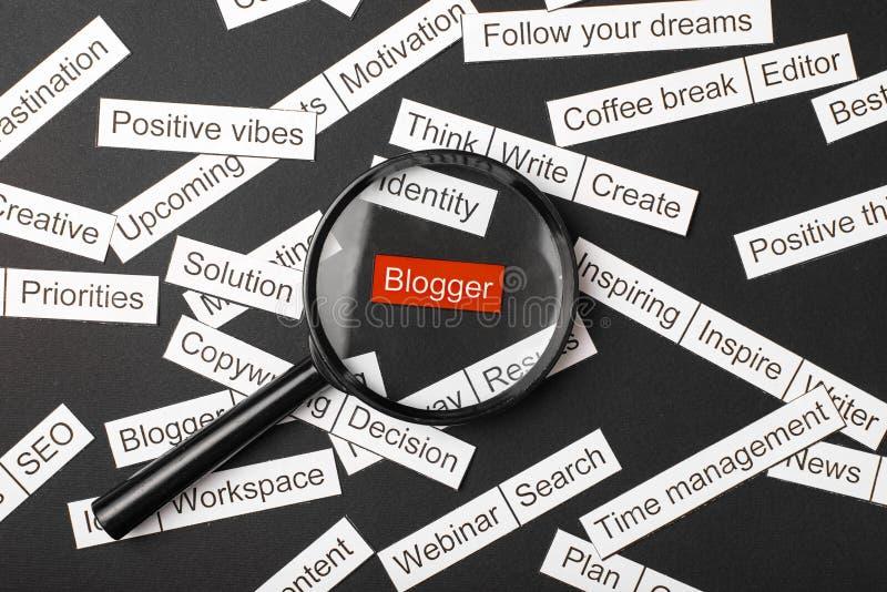 Vetro della lente sopra il blogger rosso dell'iscrizione tagliato di carta Circondato da altre iscrizioni su un fondo scuro parol immagine stock