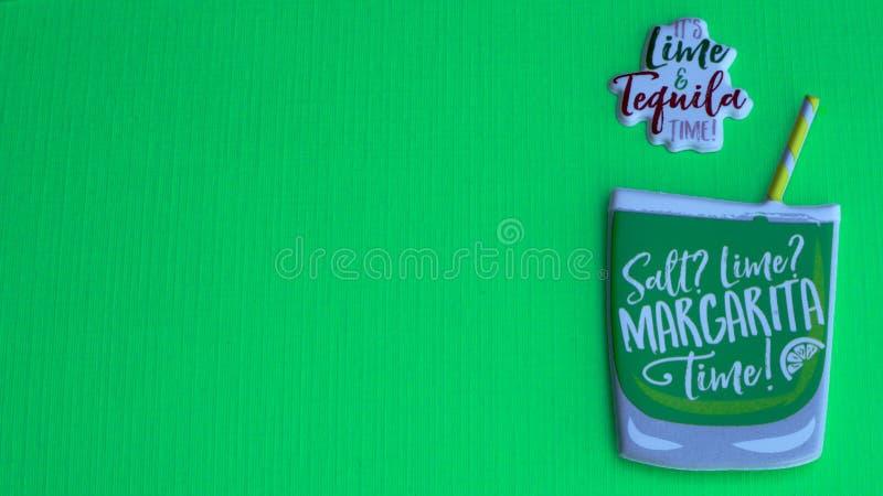 Vetro della margarita con paglia su un fondo verde