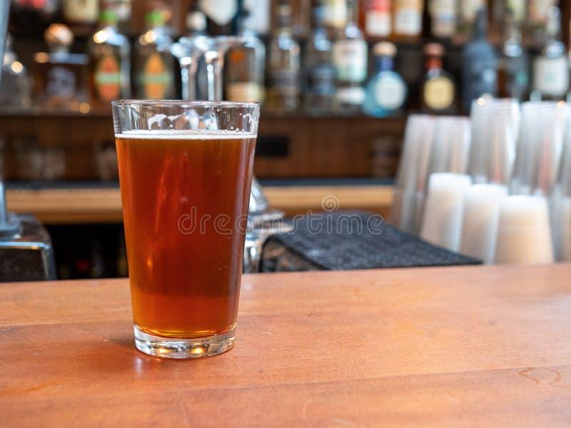 Vetro della pinta di birra che si siede sul contatore della barra nel tempo di giorno immagini stock libere da diritti