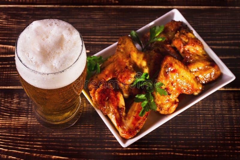 Vetro delle ali di pollo del bufalo e della birra Morsi della birra immagine stock libera da diritti