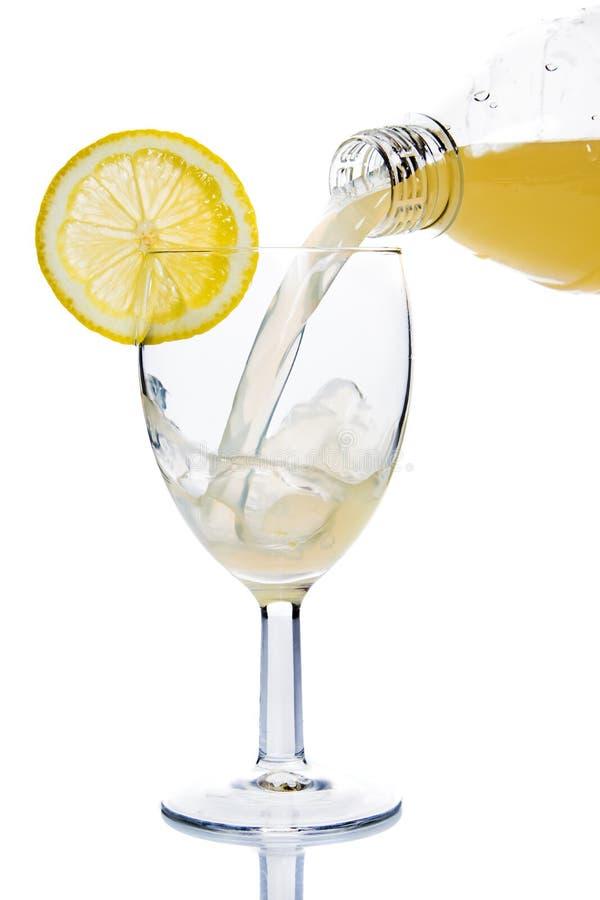 Vetro dentro versato del succo di limone fotografia stock