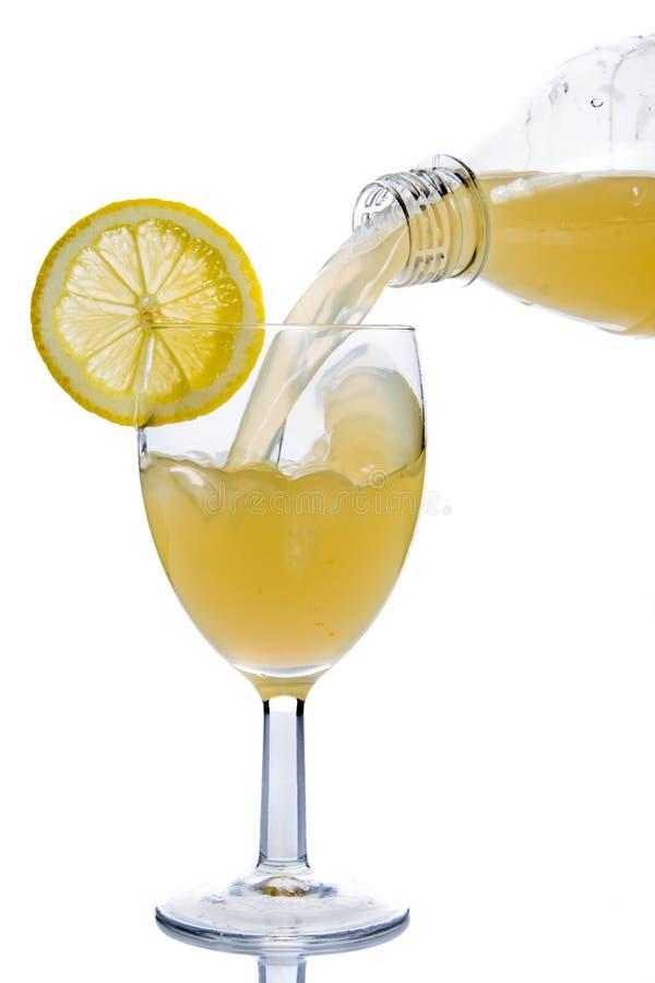 Vetro dentro versato del succo di limone fotografie stock