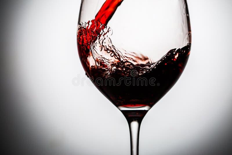 Vetro dentro versato vino rosso scuro fotografie stock