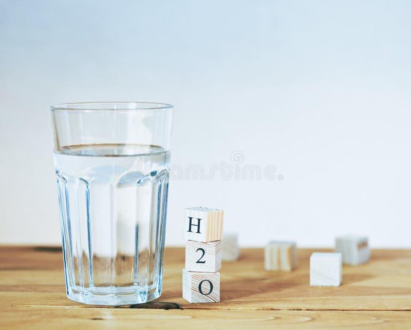 Vetro di acqua pura con la formula di H2O in blocchi di legno fotografie stock libere da diritti