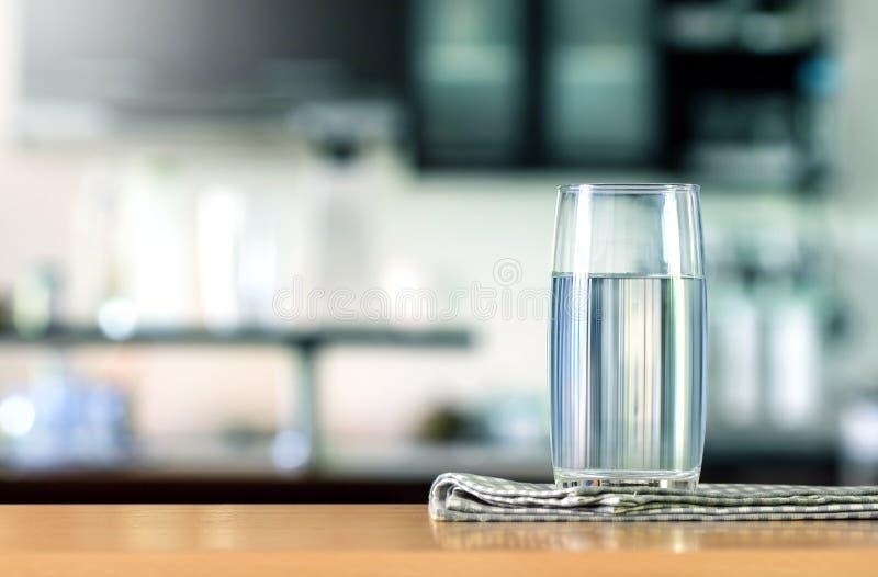 Vetro di acqua purificata sulla barra della tavola nel kitchenroom immagine stock