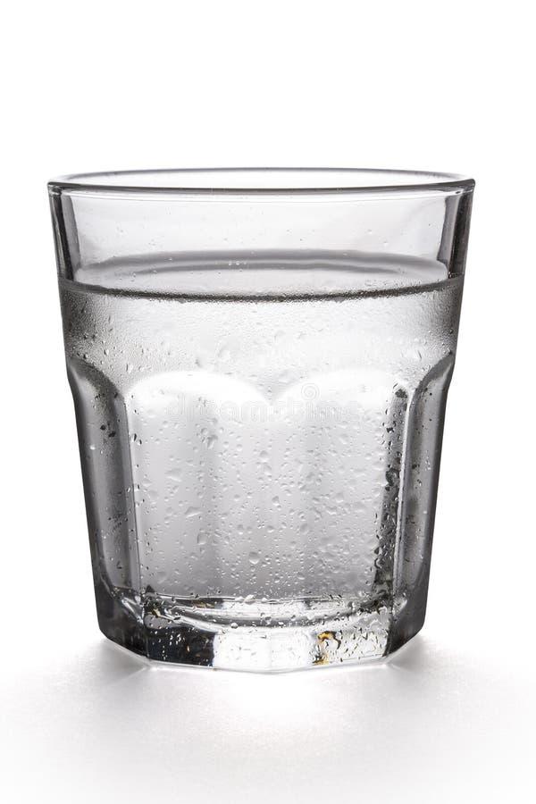 Vetro di acqua su una priorità bassa bianca fotografia stock libera da diritti