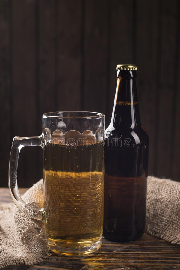 Vetro di birra, del pesce salato e dei dadi su una tavola di legno immagini stock