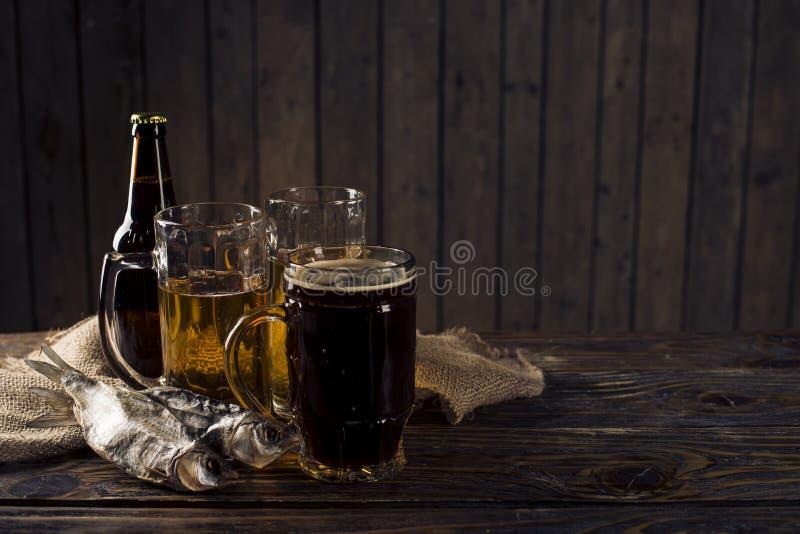 Vetro di birra, del pesce salato e dei dadi su una tavola di legno immagini stock libere da diritti