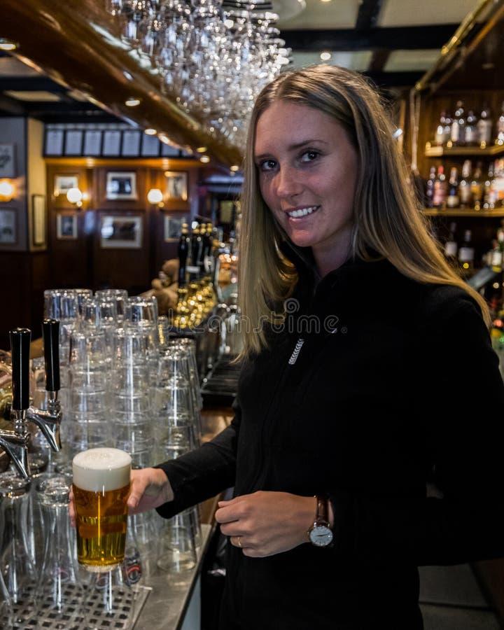 vetro di birra della tenuta del barista fotografia stock
