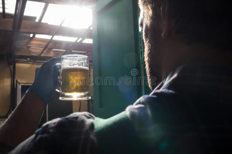 Vetro di birra della tenuta del lavoratore fotografie stock