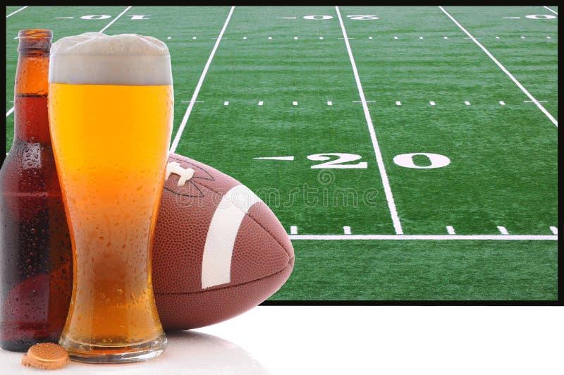 Vetro di birra e di football americano fotografie stock libere da diritti