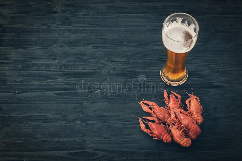 Vetro di birra fredda e dei gamberi bolliti su un fondo di legno nero fotografia stock libera da diritti