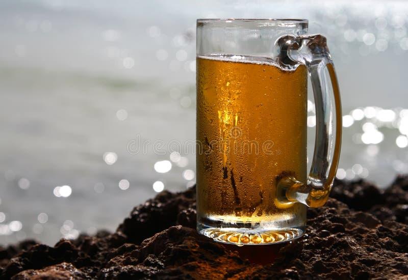 Vetro di birra fredda su un cliif, priorità bassa lucida del mare immagini stock libere da diritti