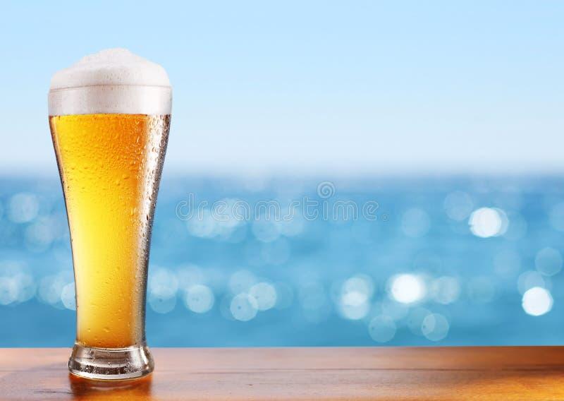 Vetro di birra fredda sulla tavola della barra al caffè all'aperto immagini stock libere da diritti