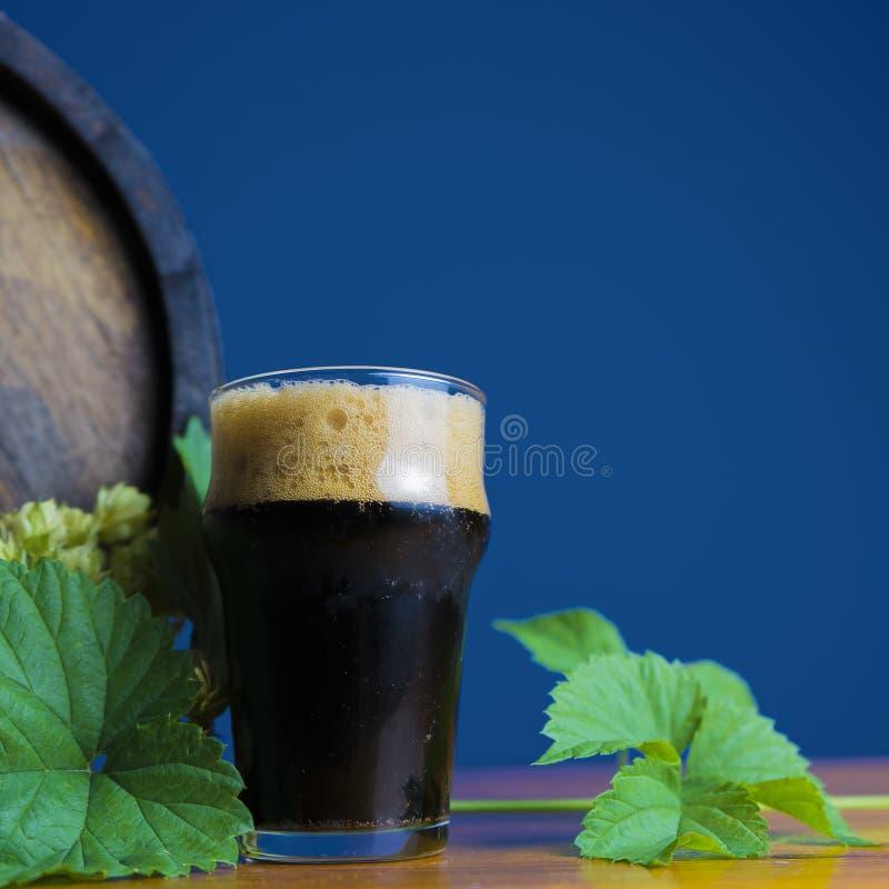 Vetro di birra di malto su una tavola di legno con le foglie del luppolo contro lo sfondo dei barilotti immagini stock libere da diritti
