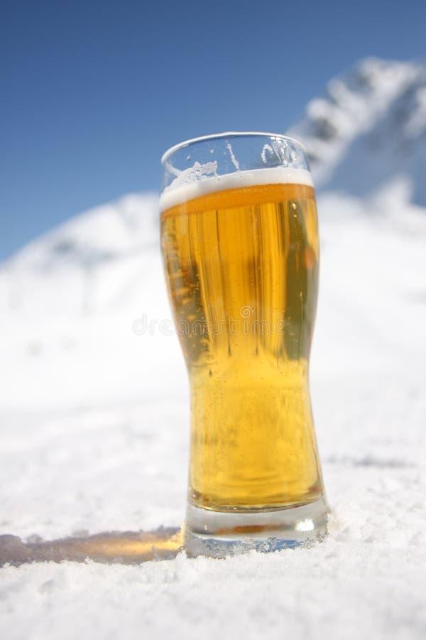 Vetro di birra sopra le alpi fotografia stock