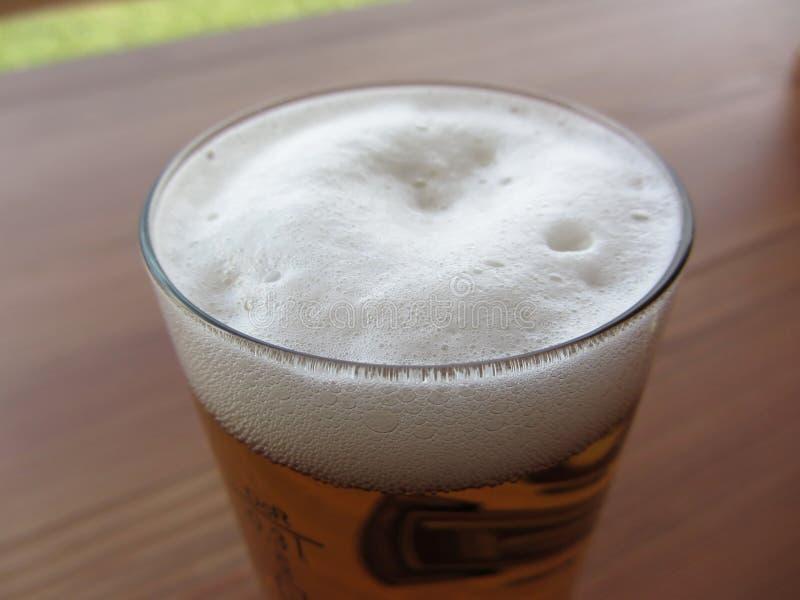 Vetro di birra sulla tabella Primo piano della schiuma della birra fotografie stock