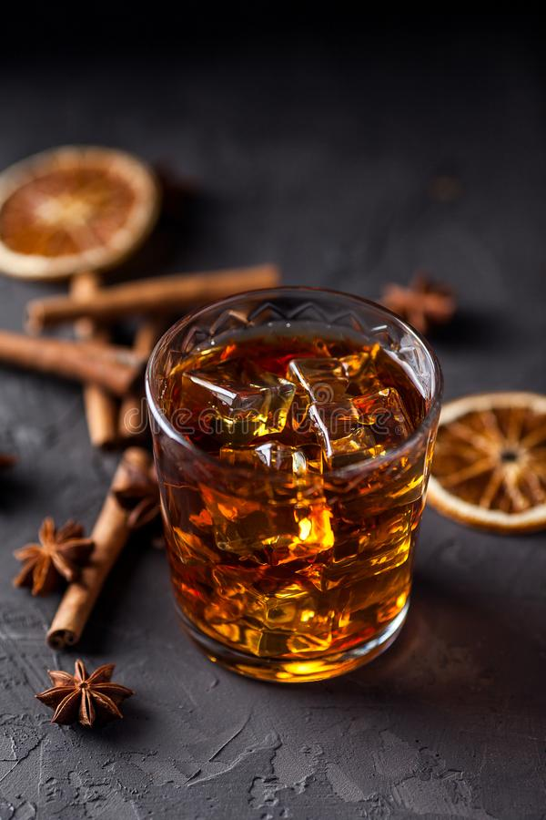 Vetro di brandy o whiskey, spezie e decorazioni su fondo scuro Concetto stagionale di feste immagini stock