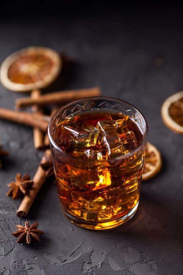 Vetro di brandy o whiskey, spezie e decorazioni su fondo scuro Concetto stagionale di feste fotografia stock libera da diritti