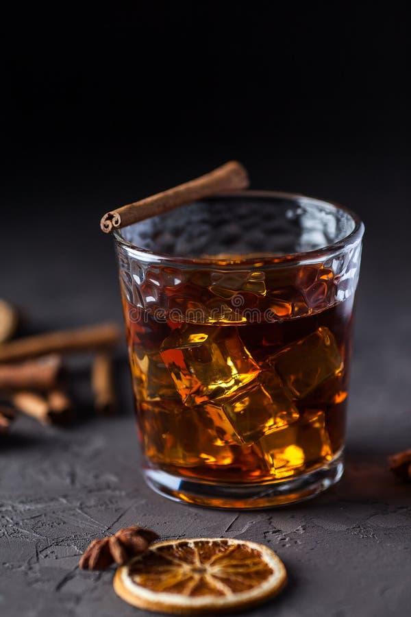 Vetro di brandy o whiskey, spezie e decorazioni su fondo scuro Concetto stagionale di feste fotografie stock